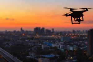 silhouette-drone-flying-city-sunset_51195-3400